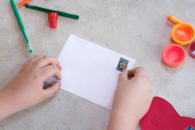 Niño jugando con un sobre blanco y un sello postal para niños, concepto de manualidades, fotografía de alta calidad