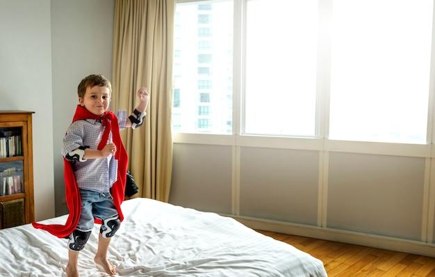 Niño jugando superhéroe en la cama