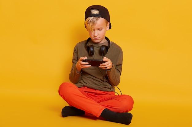Niño jugando en el teléfono mientras está sentado en el piso aislado en amarillo, niño masculino con teléfono móvil en las manos, posando con auriculares alrededor del cuello, jugando juegos en línea.
