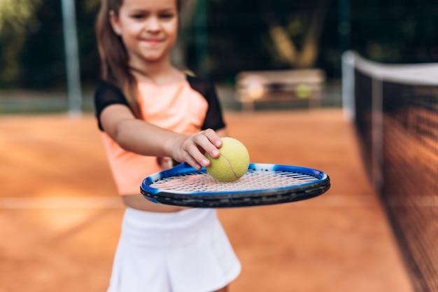 Niño jugando tenis en la cancha al aire libre