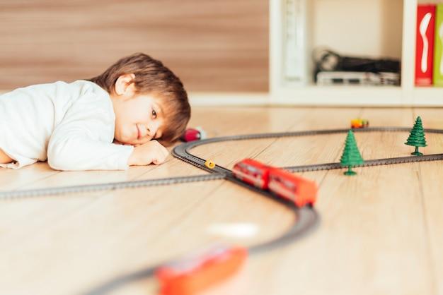 Niño jugando con tren de juguete