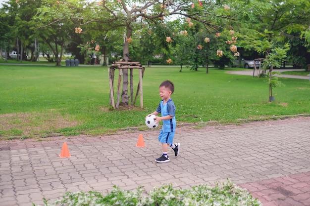 Niño de kindergarten en uniforme de fútbol está jugando fútbol