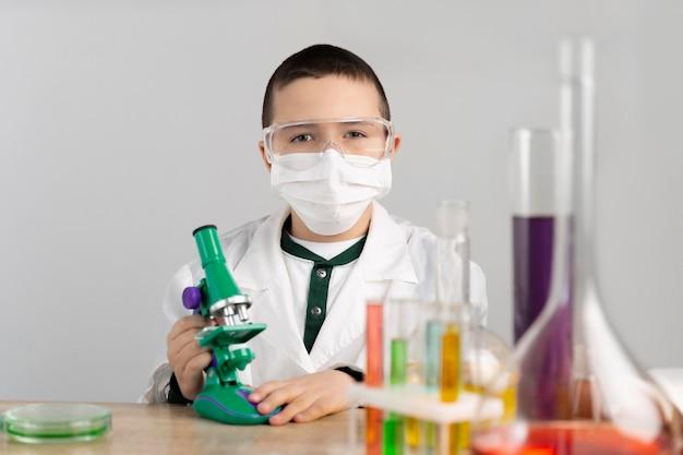 Niño en laboratorio con microscopio