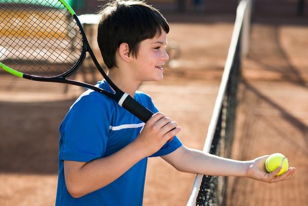 Niño de lado mostrando la pelota de tenis.