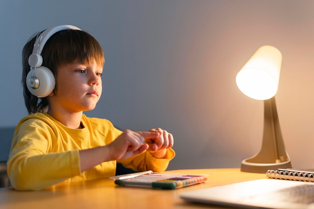 Niño de lado tomando cursos virtuales