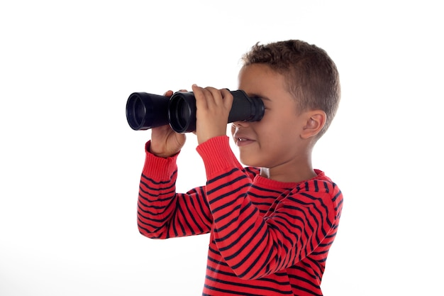Niño latino mirando a través de binoculares