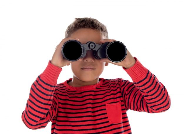 Niño latino mirando a través de unos prismáticos