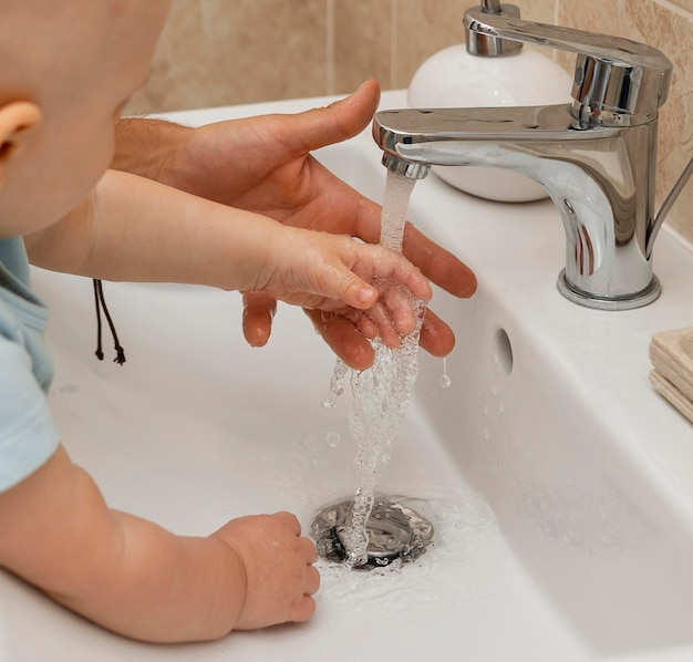 Niño lavándose las manos con la ayuda de los padres