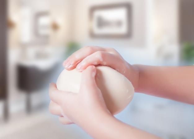 Niño lavándose las manos con una barra de jabón blanco. rutina de la mañana.