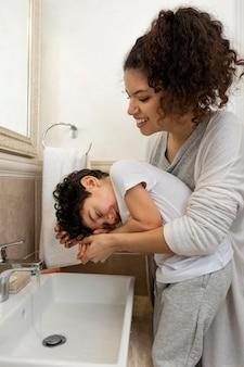 Niño lavándose las manos con su madre