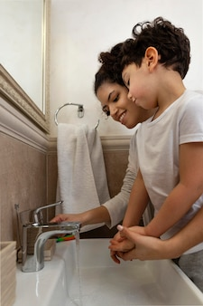 Niño lavándose las manos con su mamá