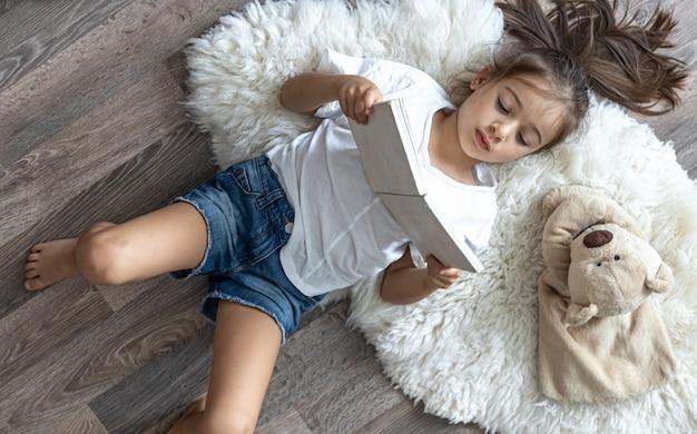 El niño lee un libro acostado en una acogedora alfombra en casa con su osito de peluche favorito.
