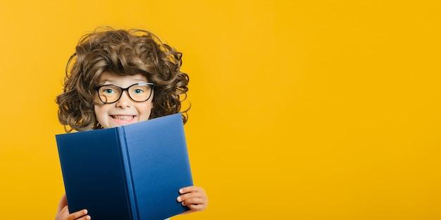 El niño lee un libro contra una pared brillante