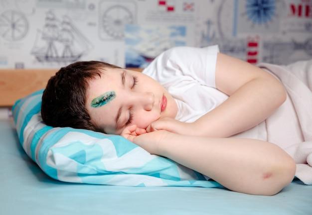 Un niño con una lesión en la cabeza está durmiendo en una cama en su habitación. el cirujano cosió la piel de su frente.