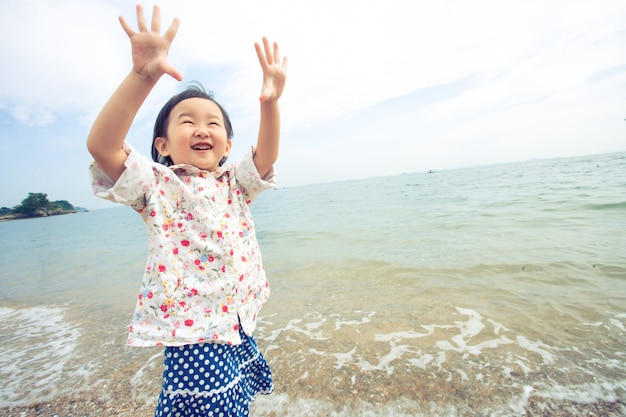 Un niño levanta la mano hacia el cielo sobre el mar. veo una sonrisa feliz
