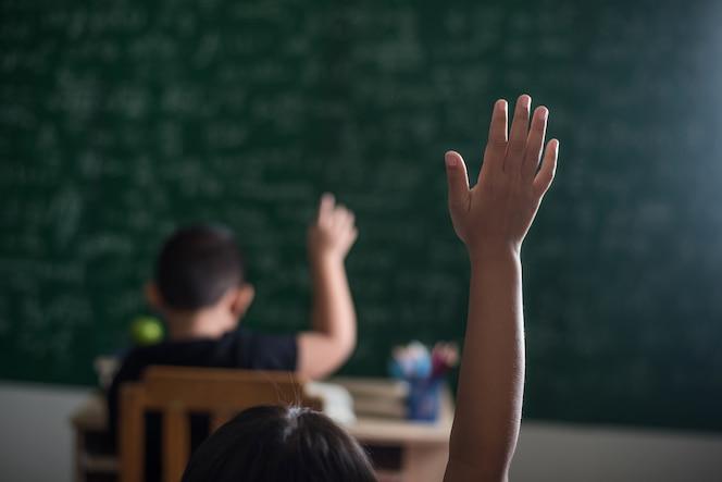 Niño levantando su mano en el aula