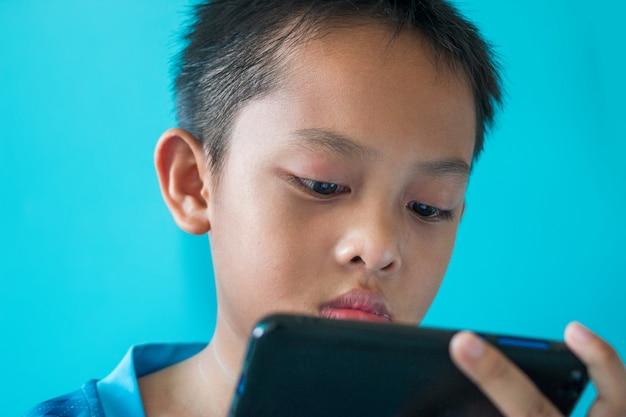 El niño está leyendo las noticias del virus corona en su teléfono inteligente.