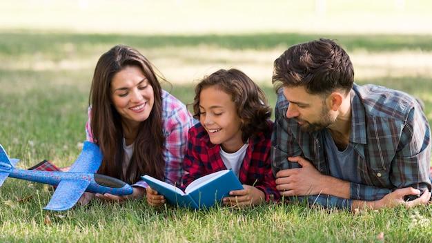 Niño leyendo en el parque con sus padres.