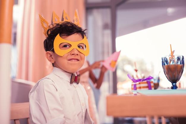 Niño con linda máscara mientras está en la fiesta de cumpleaños