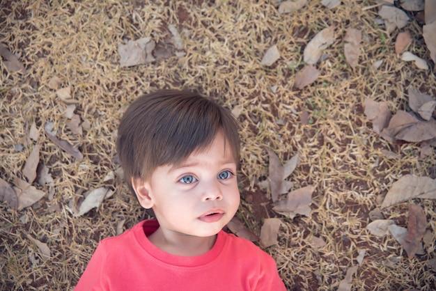 Niño lindo bebé niño - acostado en la hierba seca