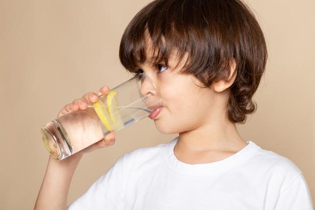 Niño lindo beber jugo de limón en rosa