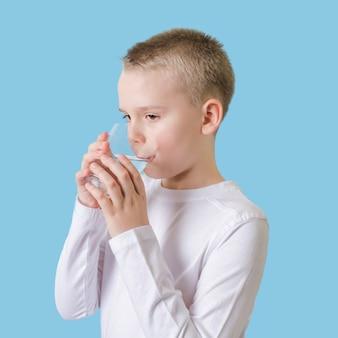 Niño lindo bebiendo agua limpia de vidrio