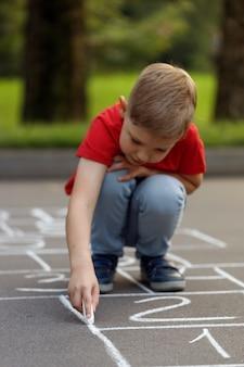 Niño lindo en camiseta roja dibujo rayuela con tiza en el patio de recreo.