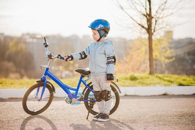 Niño lindo en casco aprende y monta en bicicleta en un día soleado al atardecer