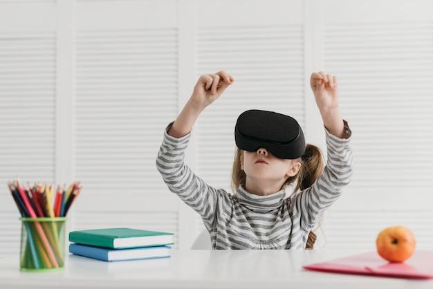 Niño lindo con casco de realidad virtual sentado en el escritorio