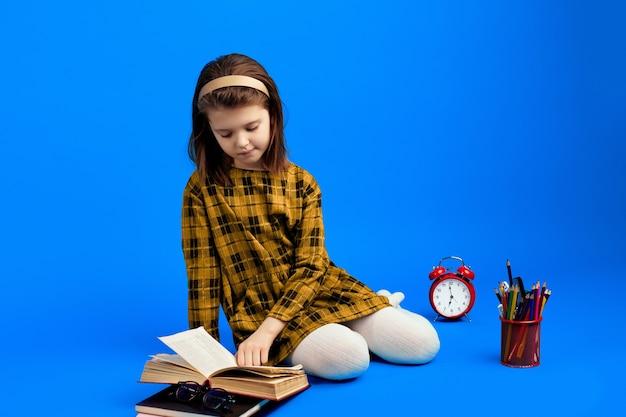 Niño lindo colegiala leyendo un libro y sentado contra el fondo azul.