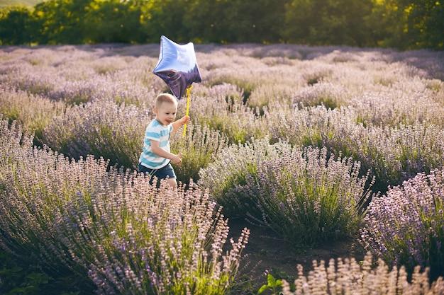 Niño lindo corriendo en el campo de flores al aire libre sosteniendo un globo.