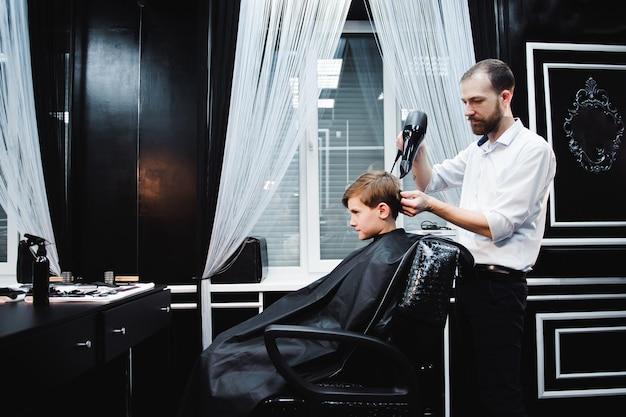 Niño lindo se corta el pelo por peluquero