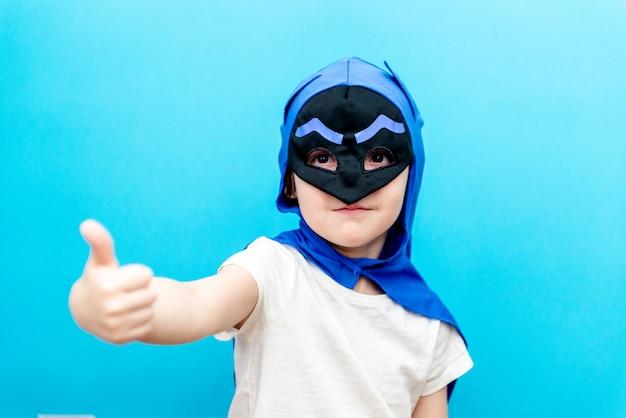 Niño lindo en un disfraz de superhéroe en una pared de color