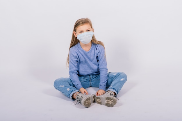 Niño lindo en un estudio, con máscara de protección, concepto de brote de coronavirus.