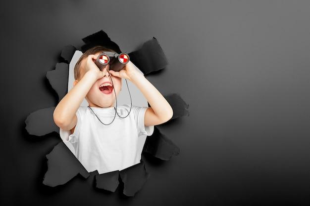 Un niño lindo feliz está mirando a través de binoculares a través de un agujero rasgado en papel negro