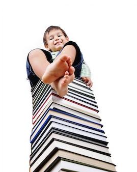 Un niño lindo y una gran cantidad de libros como una torre
