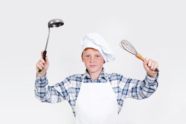 Niño lindo con herramientas de cocina