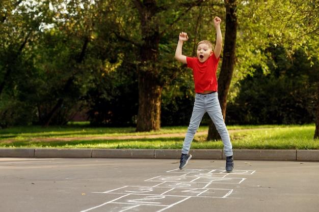 Niño lindo jugando rayuela al aire libre. juegos infantiles de la calle. enfoque selectivo.