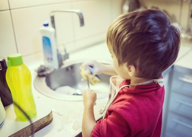 Un niño lindo lavando los platos