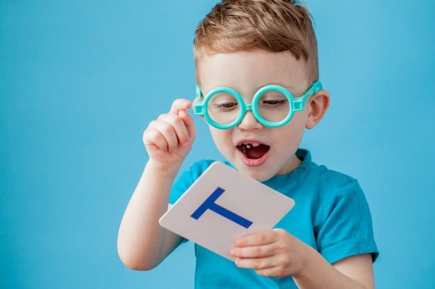 Niño lindo con la letra en el fondo. niño aprende letras.