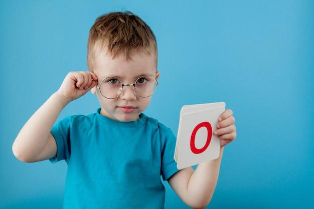 Niño lindo con la letra en la pared azul. niño aprendiendo letras. alfabeto