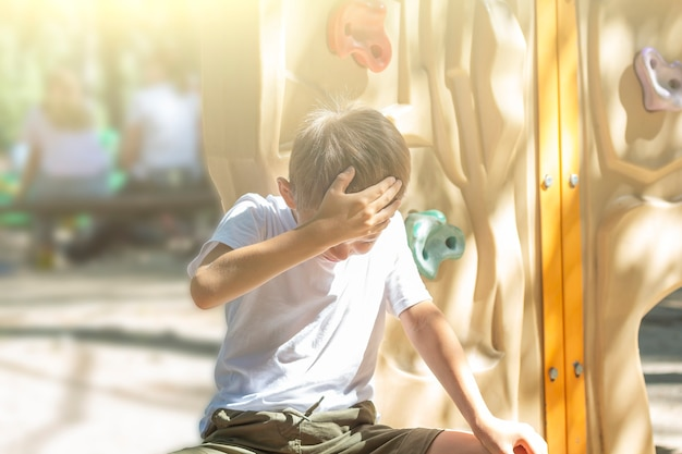Niño lindo molesto sentado después de caer