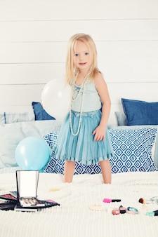 Niño lindo niña con globos en casa