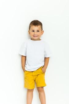Niño lindo en pantalones cortos amarillos y camiseta blanca