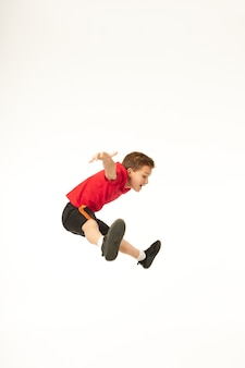 Niño lindo en pantalones cortos mirando hacia abajo y sonriendo mientras extiende las manos a los lados y salta en el aire. aislado sobre fondo blanco
