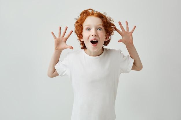 Niño lindo con el pelo de jengibre en camiseta blanca divirtiéndose en casa, haciendo estallar los ojos con la boca abierta