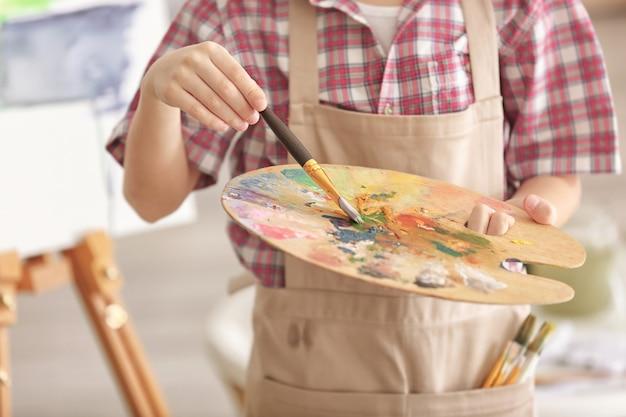 Niño lindo con pincel y paleta en estudio, primer plano