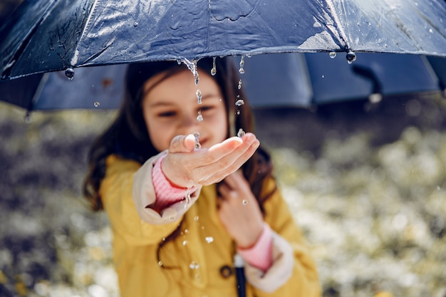 Niño lindo plaiyng en un día lluvioso