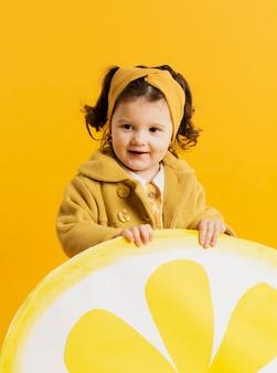 Niño lindo posando mientras sostiene la decoración de rodaja de limón