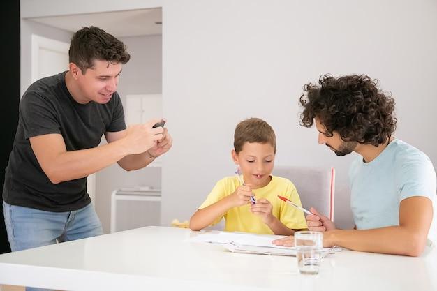 Niño lindo positivo haciendo tareas escolares en casa con la ayuda de dos papás, escribiendo en papeles. hombre tomando fotografías de su familia. concepto de familia y padres gay